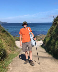 A photo of Jonathan Woods, a man wearing an orange t-shirt and beige shorts and standing with a walking stick, smiling at the camera